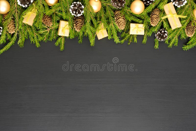 Green fir branches with cones and decorates on black wooden desk. Christmas and New Year border frame. Space for text. Border made of fir branches with cones and stock photos