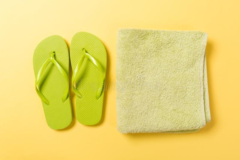 Green flip flops with towel on yellow background top view flat lay with copy space. Holiday vacation travel concept with beach sea stock photo