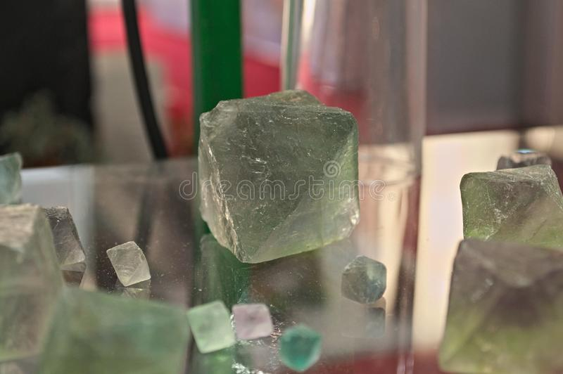 Green Fluorite Natural Octahedron Crystals on glass table royalty free stock photos