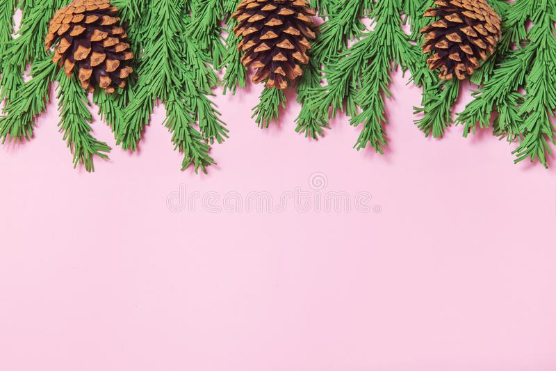 Green foam Christmas tree branch border with cones on the pink background flat lay, top view. Handmade New Year decor with copy stock image