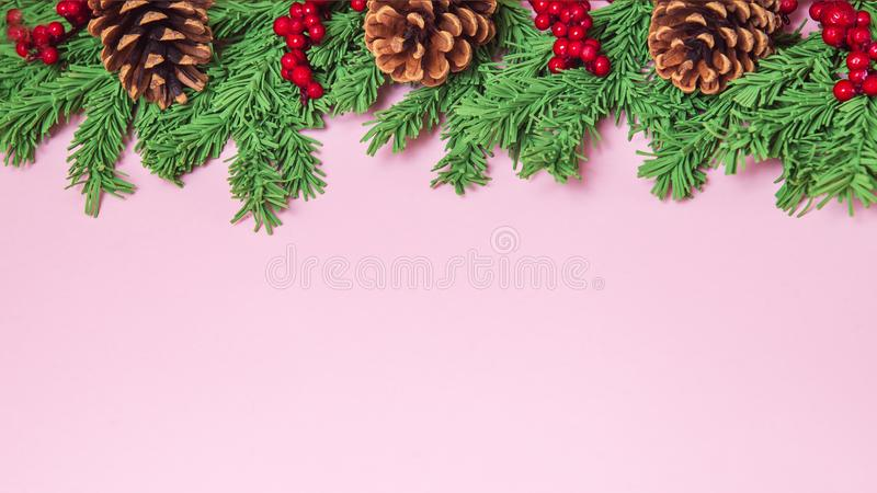 Green foam Christmas tree branch border with cones and red berries on the pink background flat lay, wide format. Handmade New Year stock images