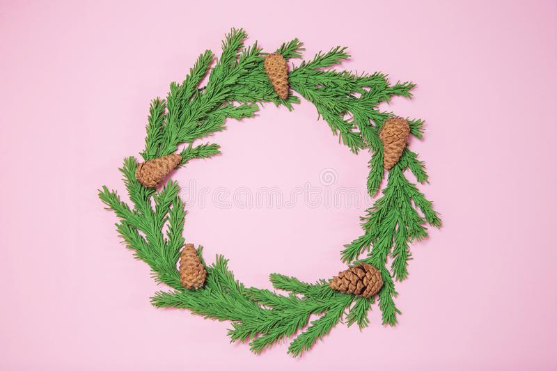 Green foam Christmas tree branch wreath on the pink background flat lay, top view. Handmade New Year decor with cones and copy stock image