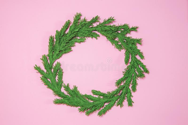 Green foam Christmas tree branch wreath on the pink background flat lay, top view. Handmade New Year decor with copy space, mock royalty free stock images