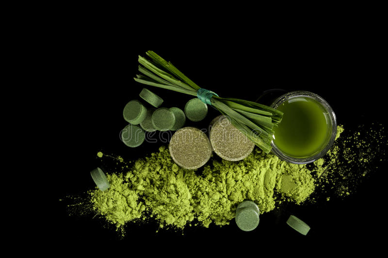Green food supplements. Green food supplements chlorella, spirulina, wheatgrass, pills, powder, tablets, grass blades and green juice on black background, top royalty free stock images