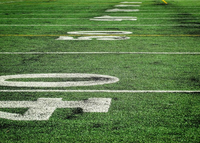Football camp low perspective. Green football camp from a low perspective showing numbers and white lines royalty free stock photography