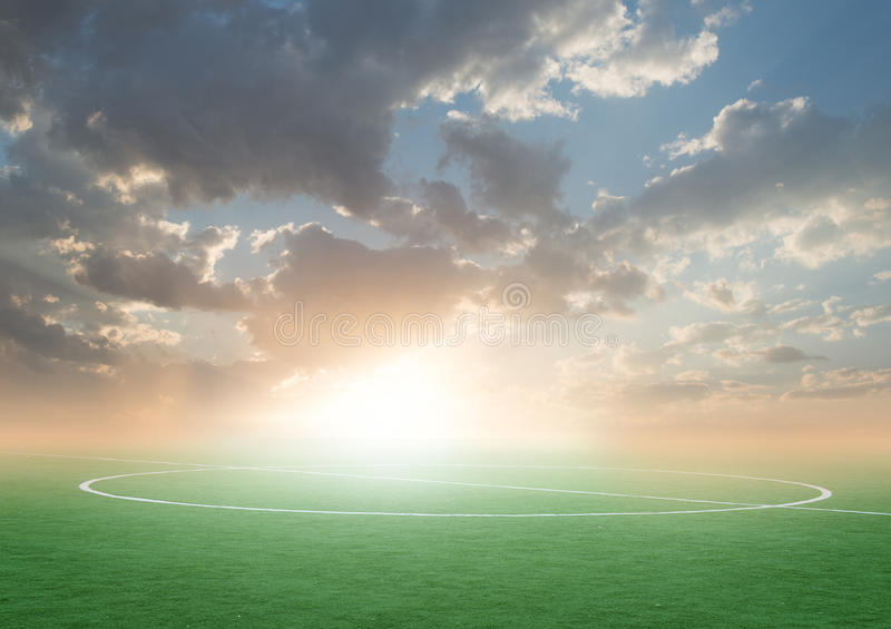 Green football soccer field with the blue sky. Sunset royalty free stock photo
