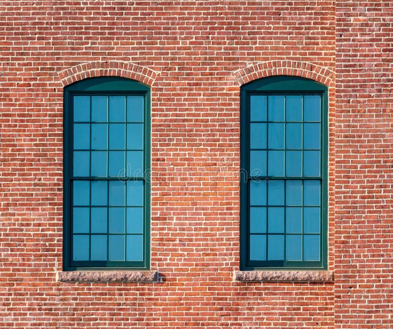 Green framed windows in a brick wall royalty free stock images