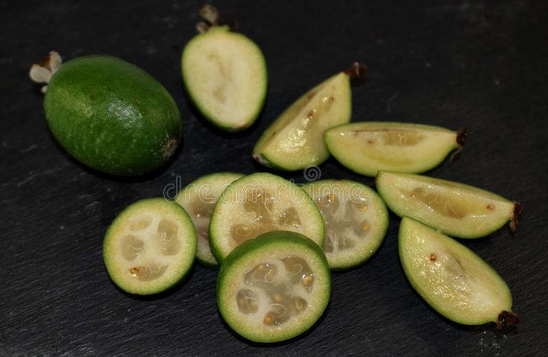 Green fresh whole and cut into pieces exotic fruit feijoa on a black background royalty free stock images