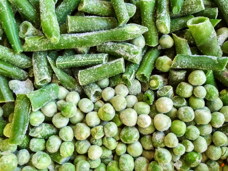 Green frozen beans and peas. Closeup frozen cut green french bean, haricot vert. Vegetable food background, healthy vegetarian. Natural nutrition stock photography