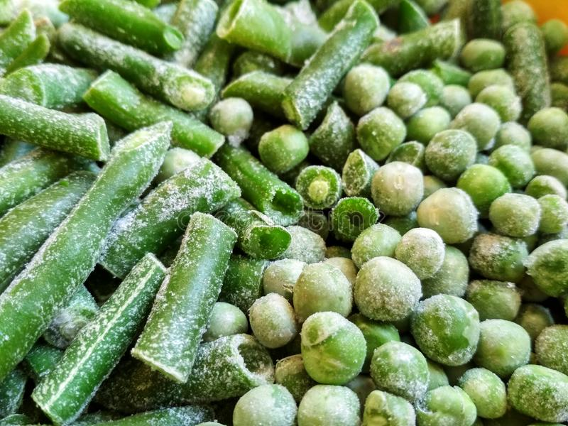 Green frozen beans and peas. Closeup frozen cut green french bean, haricot vert. Vegetable food background, healthy vegetarian. Natural nutrition royalty free stock photos