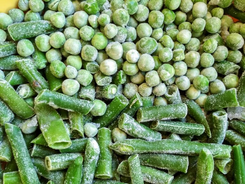 Green frozen beans and peas. Closeup frozen cut green french bean, haricot vert. Vegetable food background, healthy vegetarian. Natural nutrition stock photo