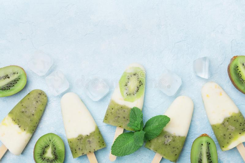 Green frozen fruity popsicles or homemade ice cream with yogurt and kiwi smoothie top view. Summer food. royalty free stock photos