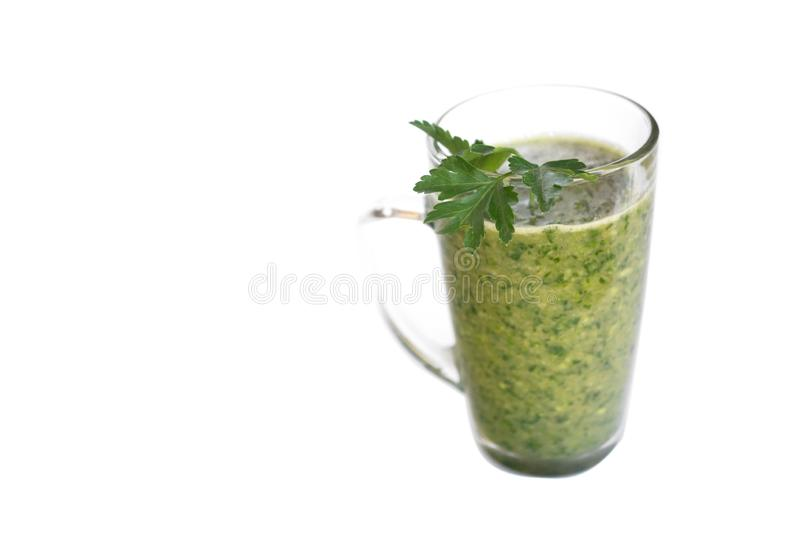 Green fruit and vegetable smoothie with a sprig of parsley in a transparent glass mug on a white background. healthy diet. food royalty free stock photography