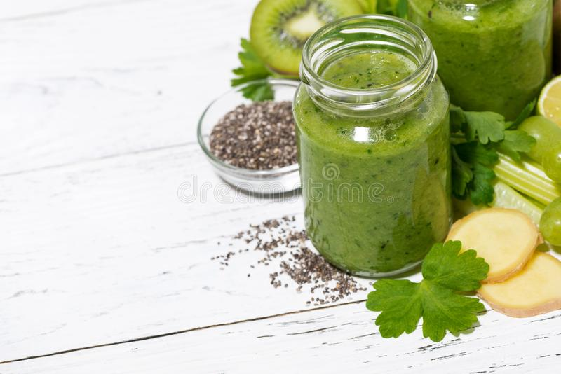 Green fruit and vegetable smoothies in jars on white table. Top view, horizontal royalty free stock photos