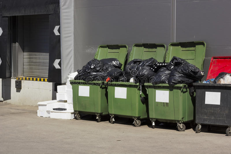 Green garbage containers near large food shop. Green garbage containers near large food city shop. Sunny day stock photos