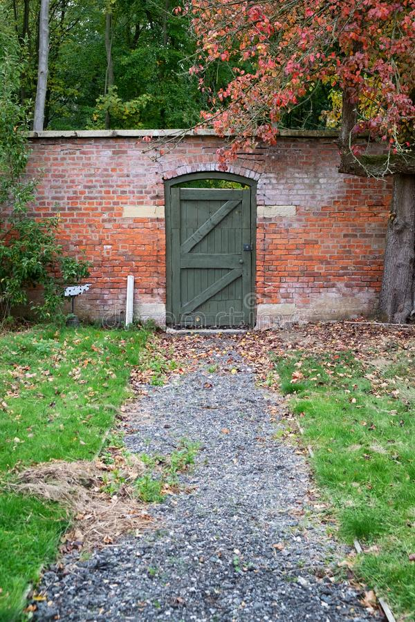 Green garden door at the end of a gravel path royalty free stock photography