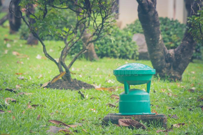 Green garden lamp on green grass in public park. royalty free stock photography