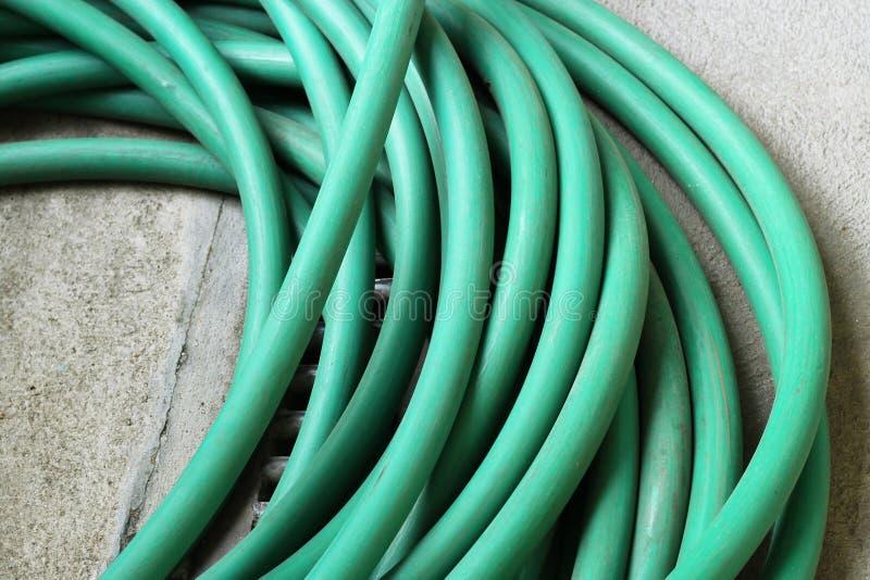 Green garden water hose. On cement floor stock photography