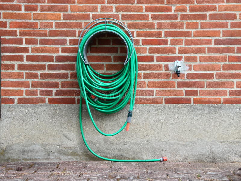 Green Garden Water Hose mounted on Red Brickwall stock photography