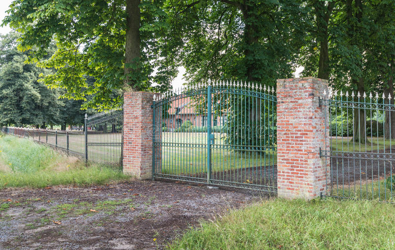 Green gate and two red pillars. stock image