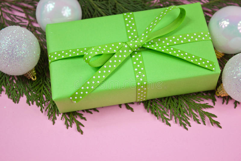 Green gift with polka dot ribbon on pink. Green gift with polka dot ribbon and Christmas decoration and cypress branch on pink stock photo