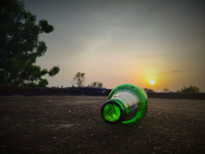 Green glass bottles of beer at sunset sky. Empty beer bottle. Inside, bottom stock image