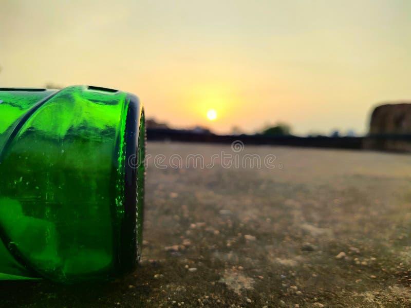 Green glass bottles of beer at sunset sky. Empty beer bottle. Inside, bottom stock photos