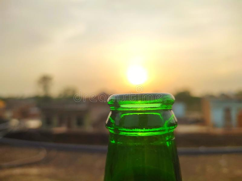 Green glass bottles of beer at sunset sky. Empty beer bottle. royalty free stock images