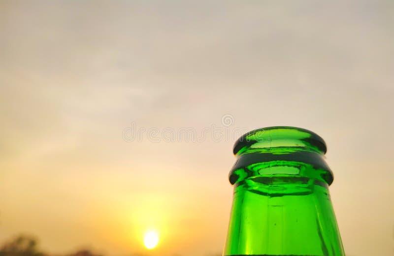 Green glass bottles of beer at sunset sky. Empty beer bottle. Inside, bottom stock photo