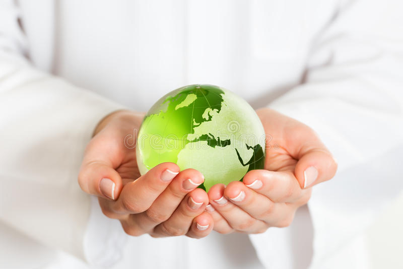 Green glass globe in hand stock photos