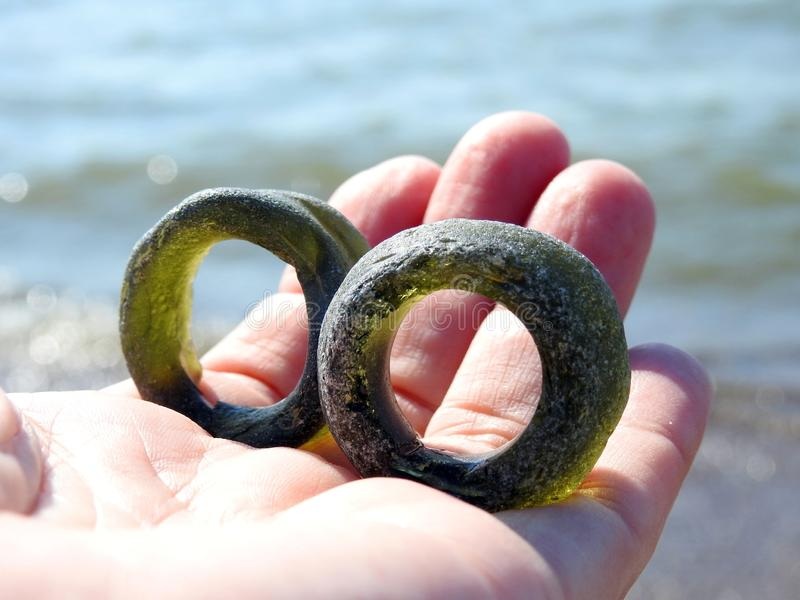 Green glass rings  in woman hand on Baltic sea coast, Lithuania. Beautiful two green glass rings   find on Baltic sea coast on woman hand in evening in sunset stock image