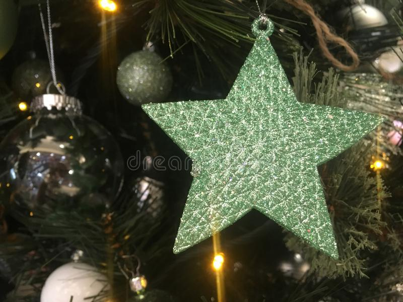 Green glitter encrusted star hanging on a Christmas tree royalty free stock photos