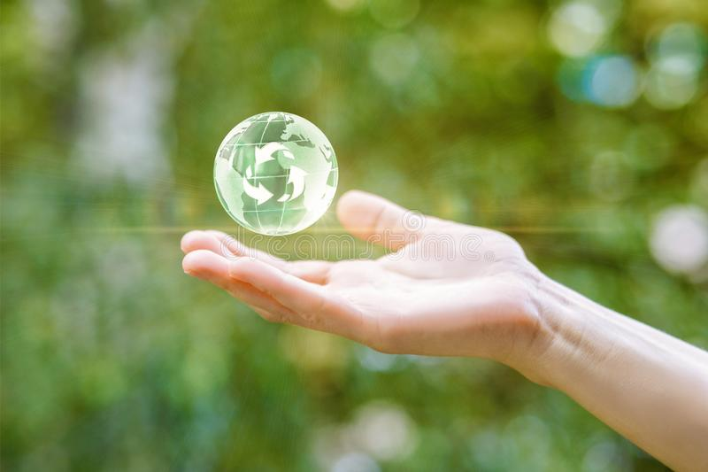 A green global map is hanging above a hand at the summer background. The concept is human influence on environment royalty free stock images