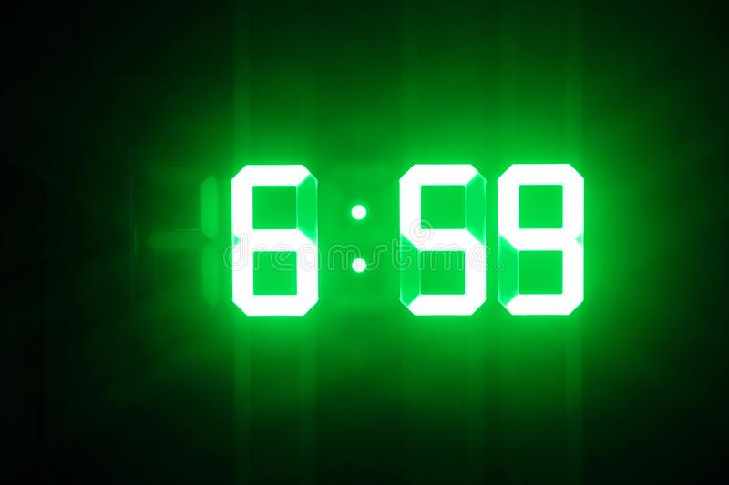 Green glowing digital clocks in the dark show 6:59 time.  royalty free stock image