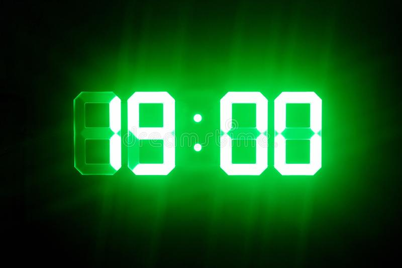 Green glowing digital clocks in the dark show 19:00 time.  stock image