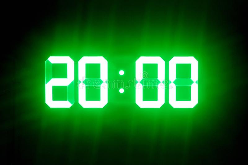 Green glowing digital clocks in the dark show 20:00 time.  royalty free stock photography