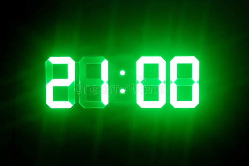 Green glowing digital clocks in the dark show 21:00 time.  royalty free stock images