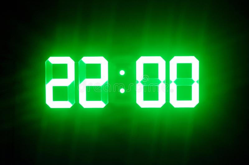Green glowing digital clocks in the dark show 22:00 time.  stock photography