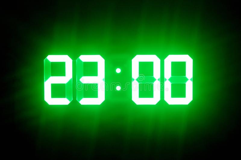 Green glowing digital clocks in the dark show 23:00 time.  royalty free stock photo
