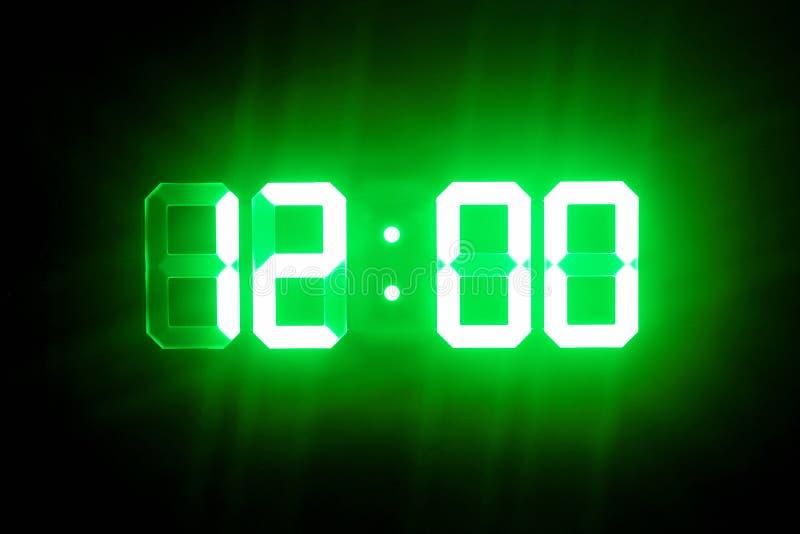 Green glowing digital clocks in the dark show 12:00 time.  stock image