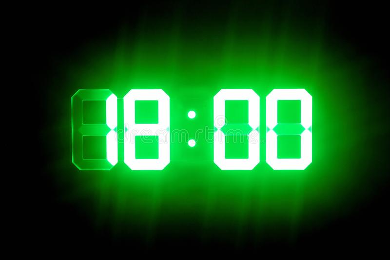 Green glowing digital clocks in the dark show 18:00 time.  royalty free stock photography