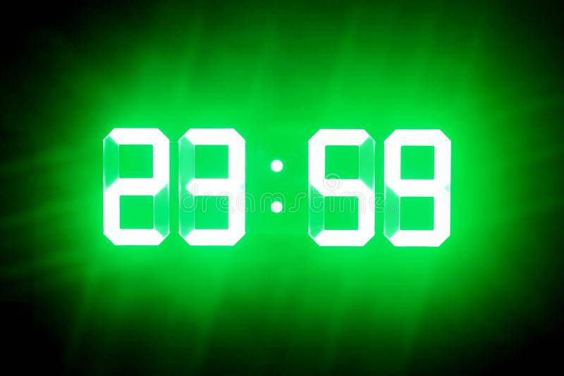 Green glowing digits in the dark show 23:59. Time is one minute to midnight stock image