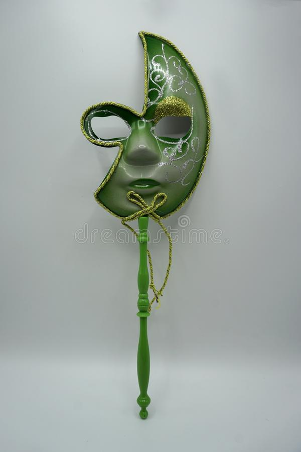 Green and gold traditional venetian carnival mask on stick on white background stock image