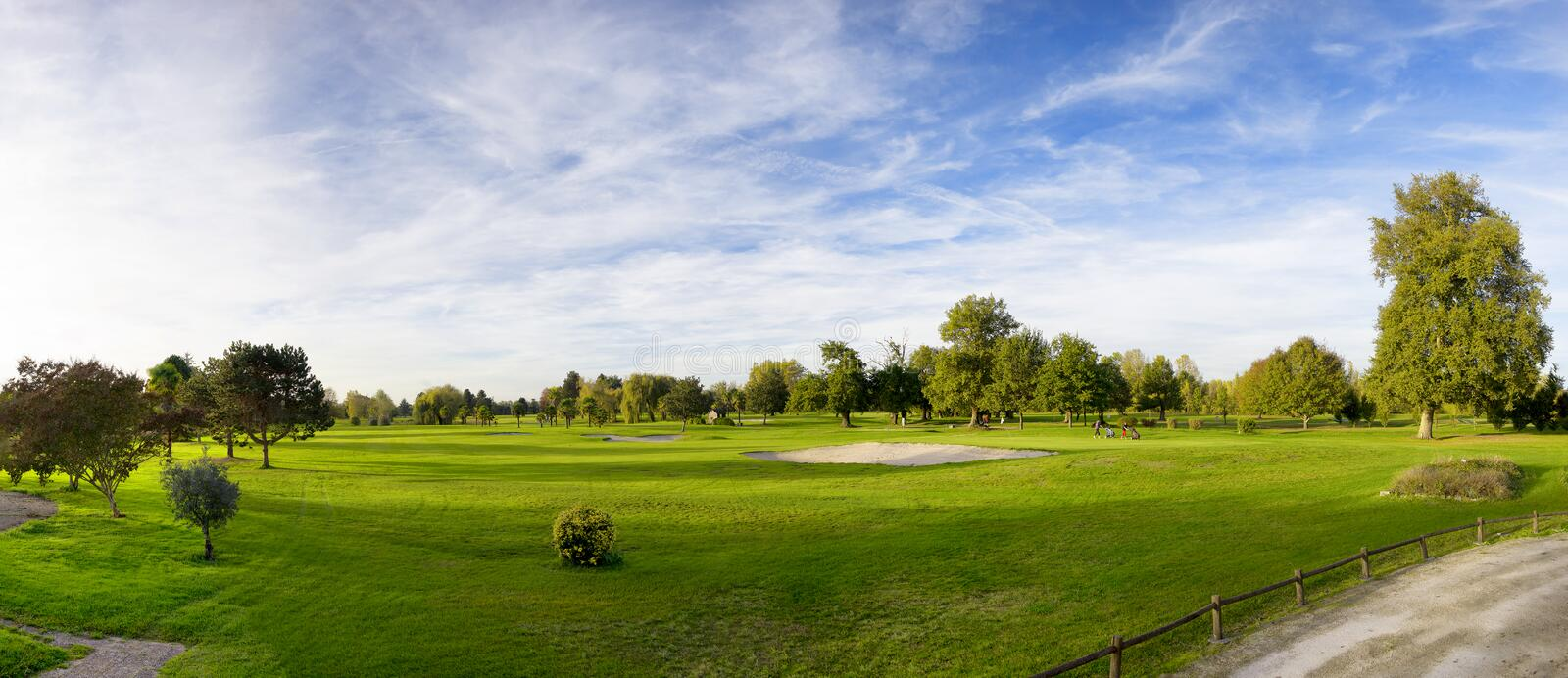 Green golf field and blue cloudy sky. A green golf field and blue cloudy sky royalty free stock image