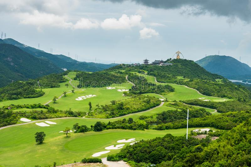A green golf field and Daxing Buddhist temple in the valley and mountains background at Shenzhen Overseas Chinese Town East OCT. East in Guangdong, China. A royalty free stock photos