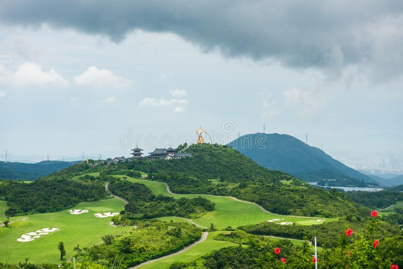 A green golf field and Daxing Buddhist temple in the valley and mountains background at Shenzhen Overseas Chinese Town East OCT. East in Guangdong, China. A stock image