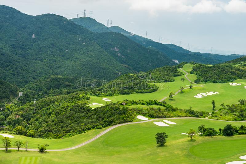 A green golf field in the valley and mountains background at Shenzhen Overseas Chinese Town East OCT East in Guangdong, China. A. Resort with three themed parks royalty free stock images