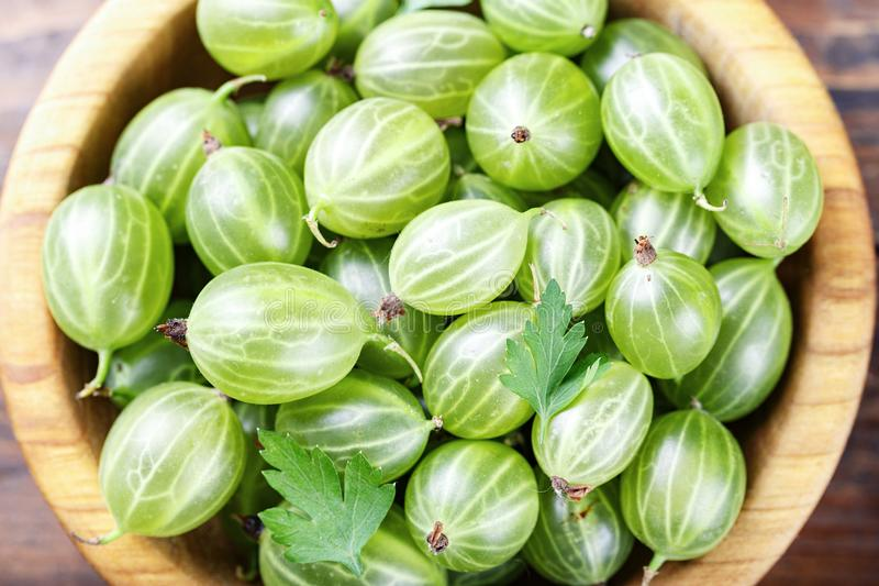 Gooseberries top view. Green gooseberry in a wooden plate on a wooden background stock photography