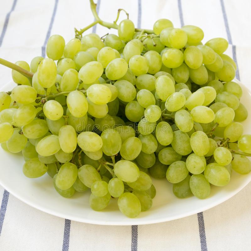 Green grape on a white plate, side view. Closeup royalty free stock images