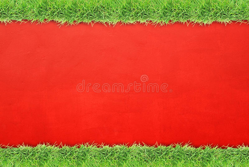 Green grass border on cement wall background. Green grass border on red cement wall background stock images